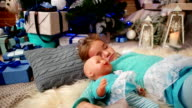 little cute girl sleep, near the fireplace where the fire burns, hugging a doll, The child sleeps near a Christmas tree, sweet sleep in the living room, family New Year's Eve video