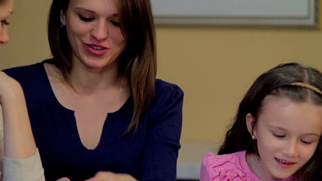 Little daughter bored reads magazine, happy mother chats friend video