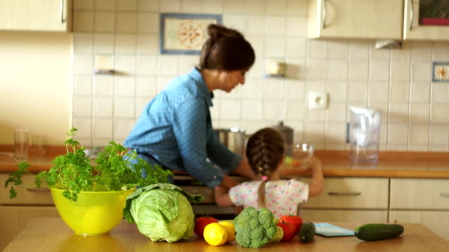 A little daughter helps her mother cook in the kitchen. Mom took the girl in her arms and they cook soup together. video