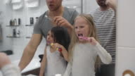 Little daughters enjoying brushing teeth with gay parents video