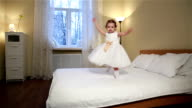 Little fidget. Cute little girl in white dress jumping on the bed in the bedroom video