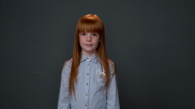 Little ginger girl coming closer, gray background video