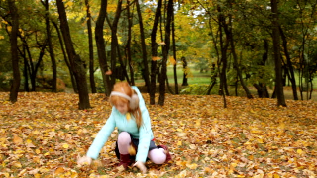 Little ginger girl playing with the autumn leaves video
