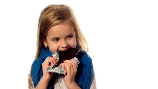 Little girl a blonde eats a chocolate video