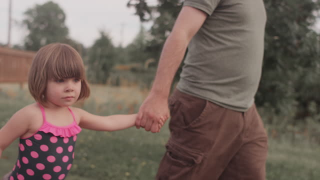 A little girl and her dad walk hand in hand down a park trail video