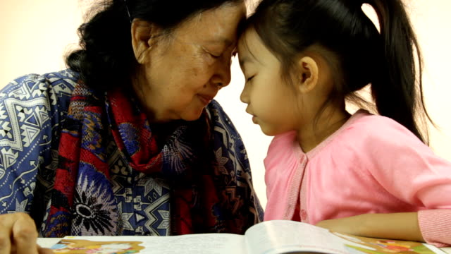 Little girl and her grandma smiling with their eyes closed and their heads against each others video