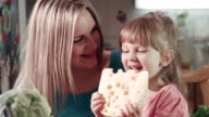 Little girl and her mother biting cheese with holes video