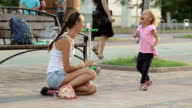 Little girl and her mother having fun with chalk in the park video