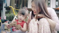 Little girl and her mother playing sand in the playground video