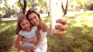 Little girl and mom smiling taking a selfie on phone video