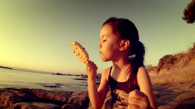 Little Girl At The Beach in Sunset Eating Ice Cream and Get Messy. video