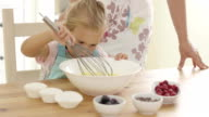 Little girl baking with her mother video