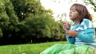 Little girl blowing bubbles video