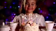 Little girl blowing out the candles of Birthday cake video