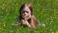 Little girl blows dandelion in meadow video