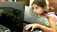 little girl child playing in the notebook online game laptop video