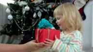 Little girl chooses a gift near the Christmas tree video