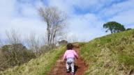 Little girl climb on a hill video