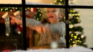 Little Girl counting Snow falling through window at Christmas video