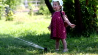 Little girl dabbles with Sprinkle hot day. video