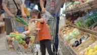 Little girl doing grocery shopping with father video
