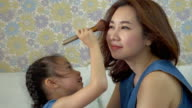 Little girl doing makeup to her mother video