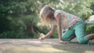 A little girl drawing on pavement with chalk video