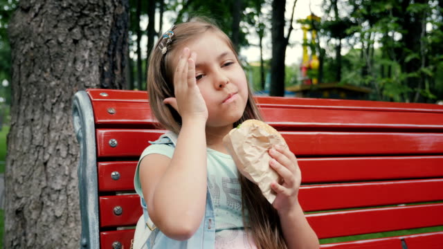 Little Girl Eating a Hamburger In the Park video