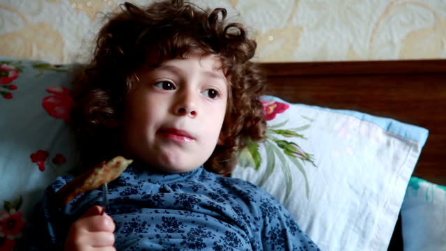 Little girl eating a pancake in the bed video