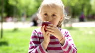 Little girl eating apple on a kids playground video