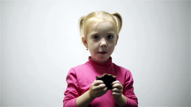 Little girl eating chocolate isolated on gray background video