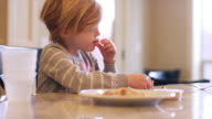 A little girl eating crackers at the kitchen counter, slow motion video