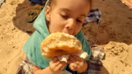 Little Girl Eating Donut At Beach. video