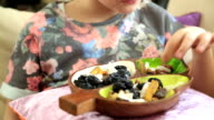 Little girl eating dried fruit video