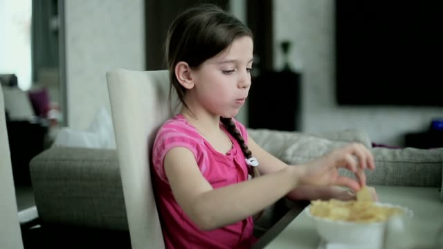 Little girl eating potato chips video