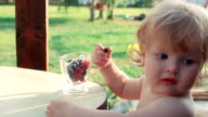 Little girl eating raspberries and blueberries from a bowl video