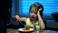 Little girl eats and watches cartoons on the computer. video