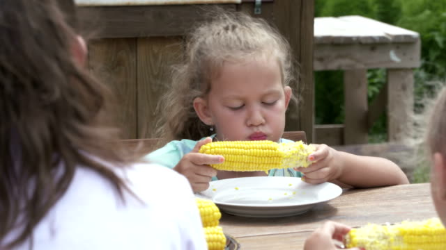 Little girl eats corn on the cob at the outdoor dining table video
