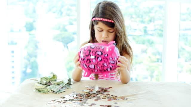 Little girl emptying her pink piggy bank video
