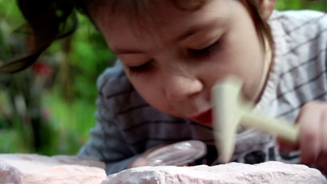 Little girl explores the stone with  magnifying lens and  hammer video
