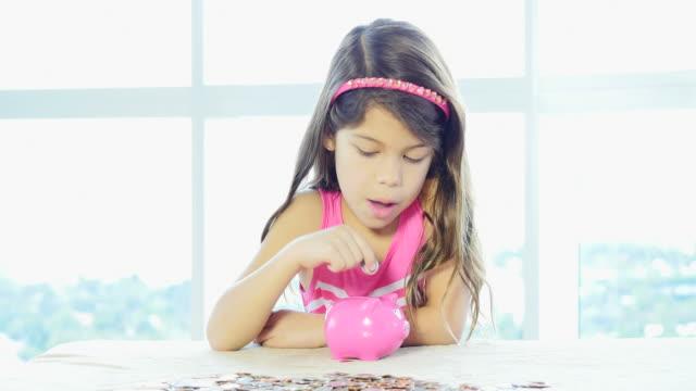 Little girl filling up piggybank video