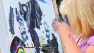 LIttle girl finger paints outside video