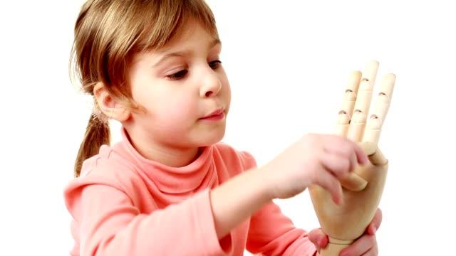 Little girl flexes fingers of human hands model video