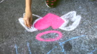 little girl fun drawing angel heart on street video