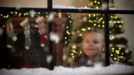 Little Girl gazing at Snow falling through window at Christmas video
