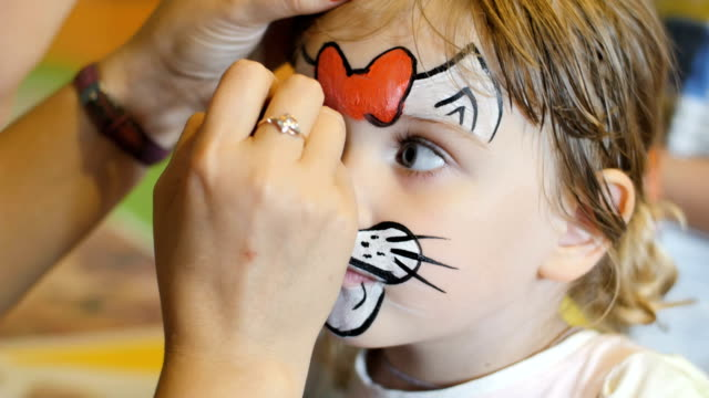 Little girl get painted face as a cat for a carnival video