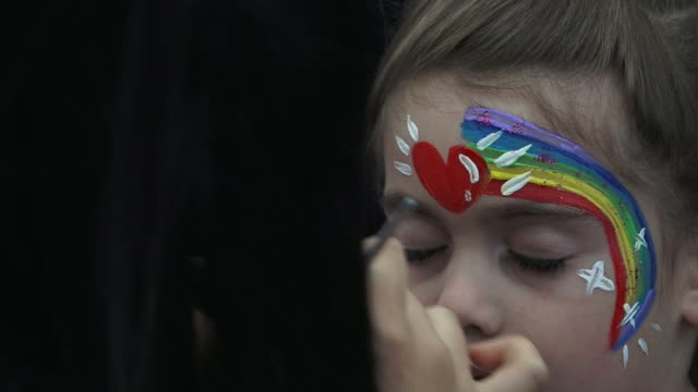 Little girl getting her face painted with rainbow video