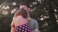 A little girl giving her father a huge hug outside video