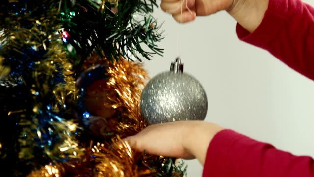 Little girl hangs on a Christmas tree ball video