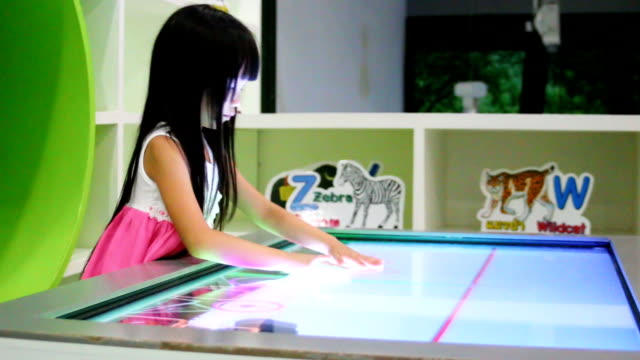 A little girl having fun play and touch games video